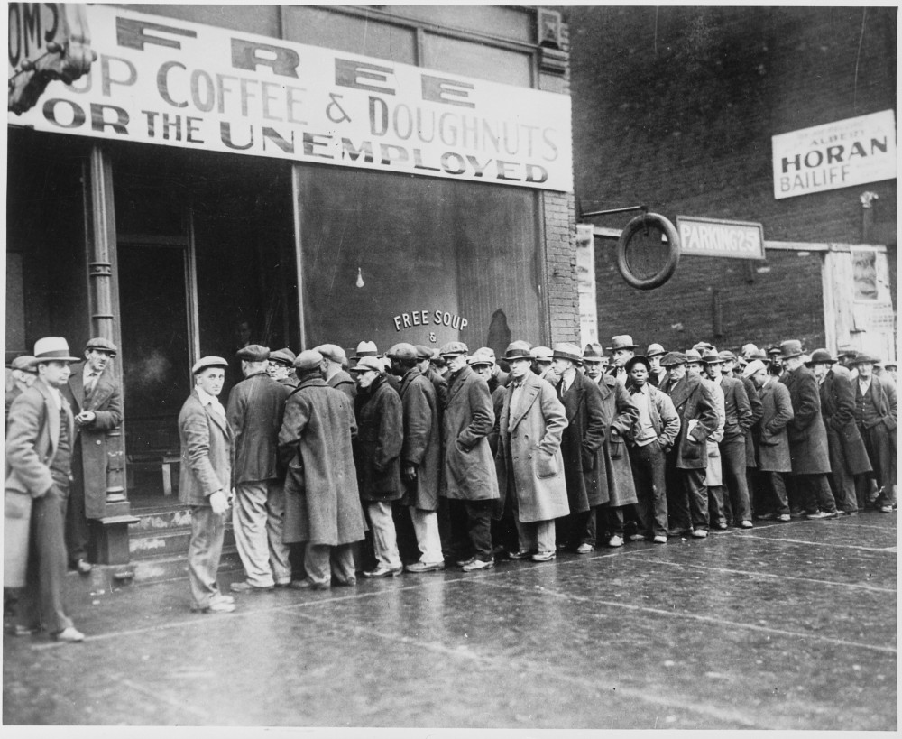 A line of men in front of a building that advertises free soup.