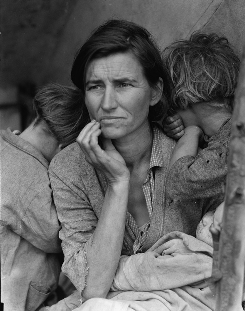 A woman looks off into the distance. Two children are burying their faces in her shoulders.
