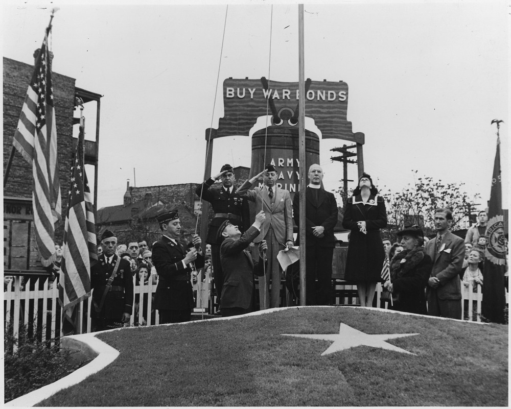 Soldiers salute and citizens stand respectfully as an American flag is either raised or lowered. A sign reads Buy War Bonds.