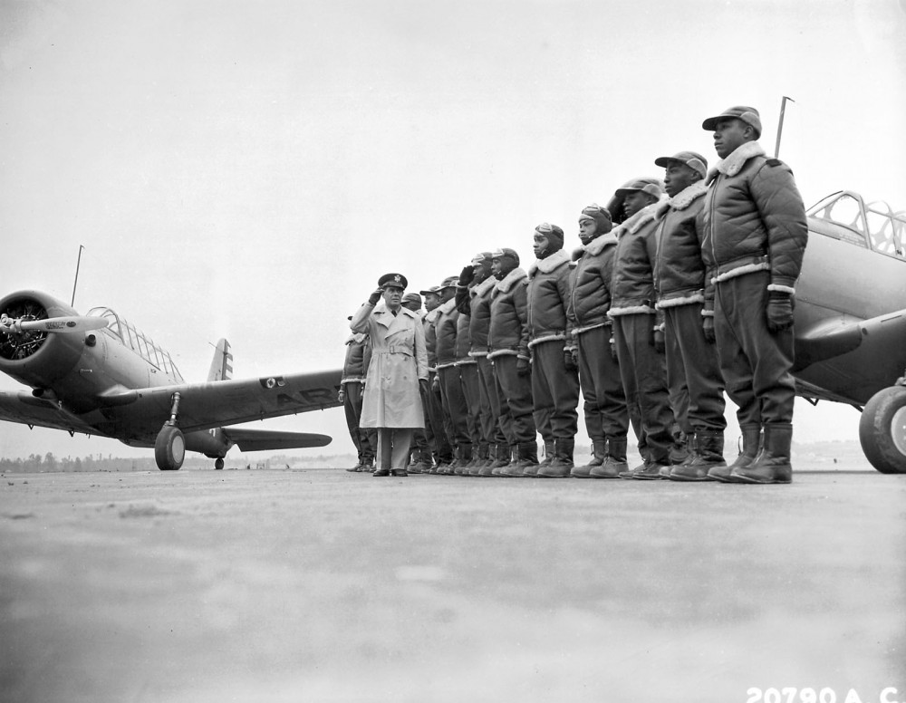 A line of black pilots standing at attention.