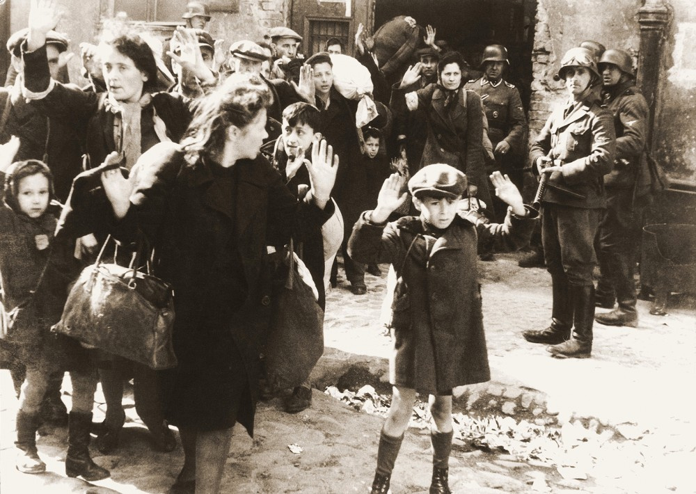 A group of women and children with their hands up walking past soldiers with guns.
