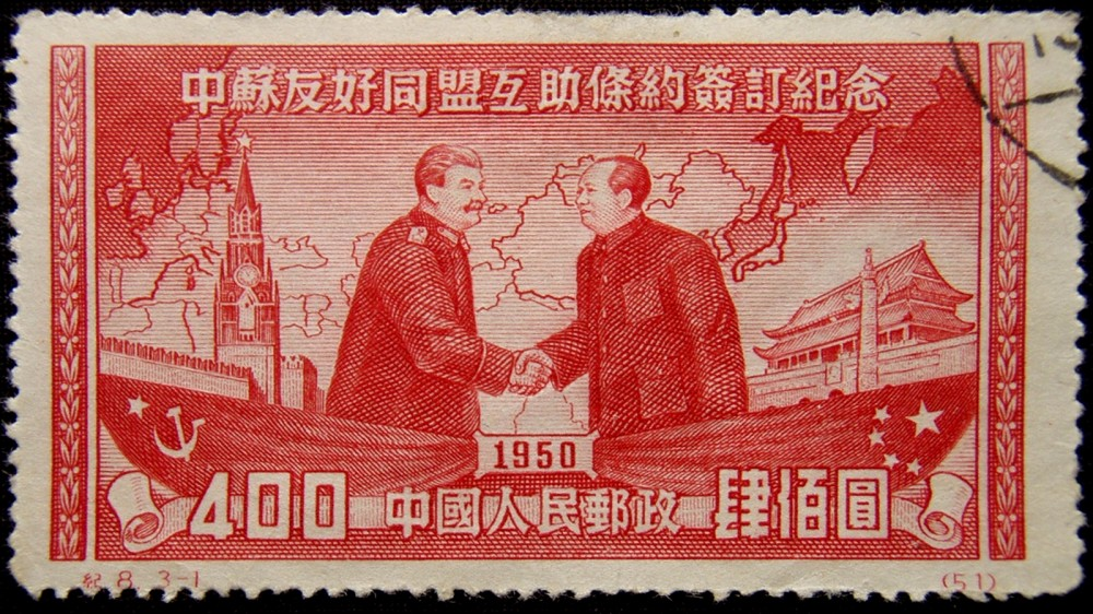 A stamp with a red-ink drawing of Joseph Stalin and Mao Zedong shaking hands.