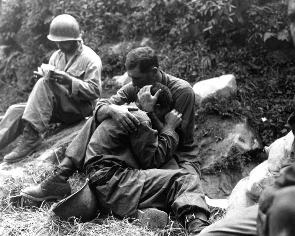 A photograph of one soldier holding and comforting another soldier.