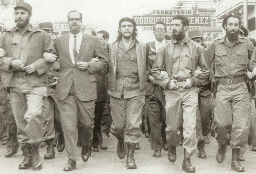 Photograph of a line of Cuban men with their arms linked. Two of the men are Fidel Castro and Che Guevara.