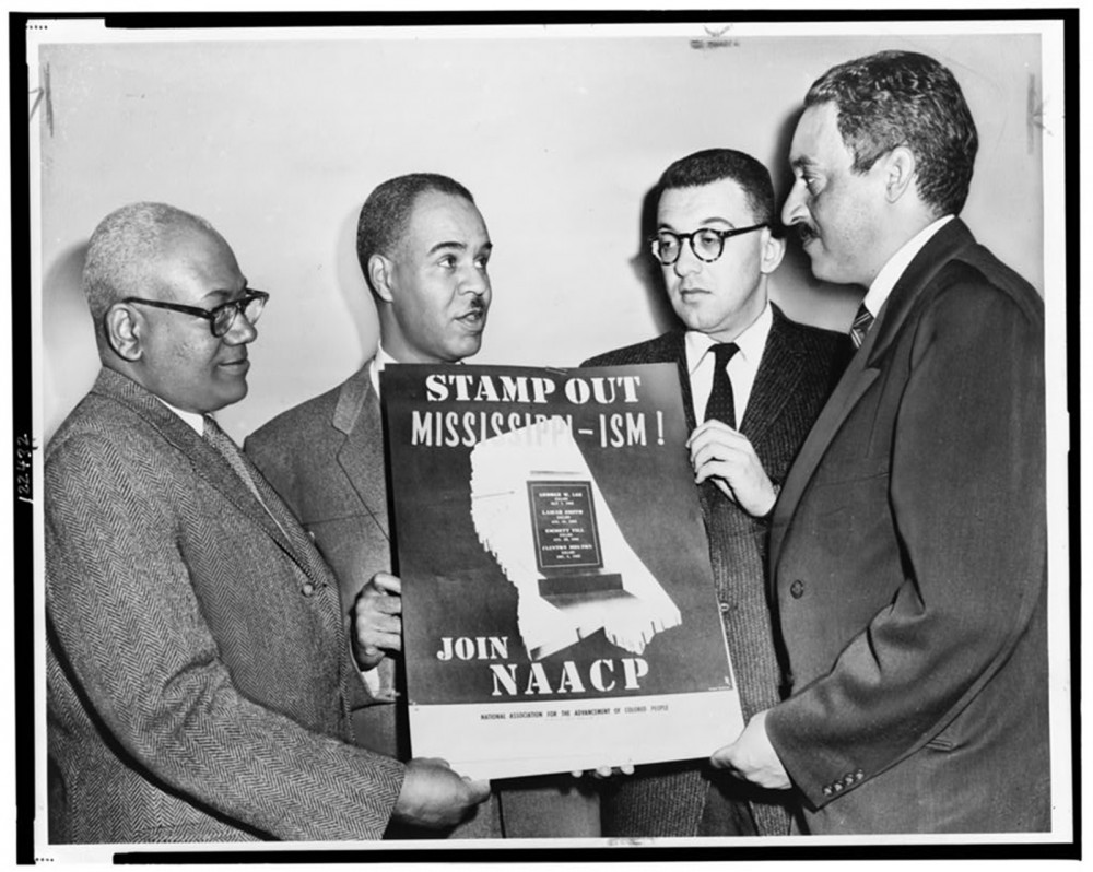 Four men holding a poster that says Stamp Out Mississippi-ism, Join NAACP.