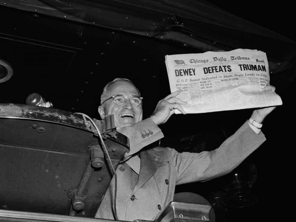 Thomas E Dewey holding a newspaper that says Dewey Defeats Truman.