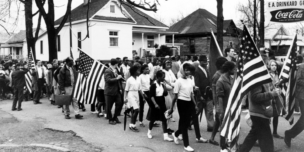 People, mostly black but a few white, marching through a town. Many are holding American flags.