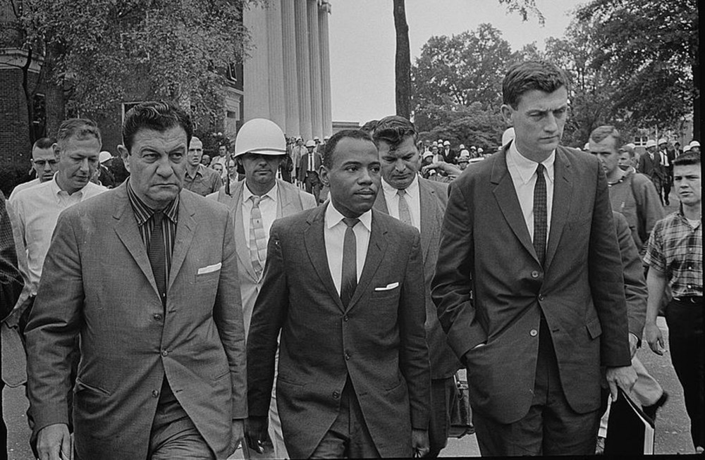 A black man wearing a suit escorted by other men wearing suits.