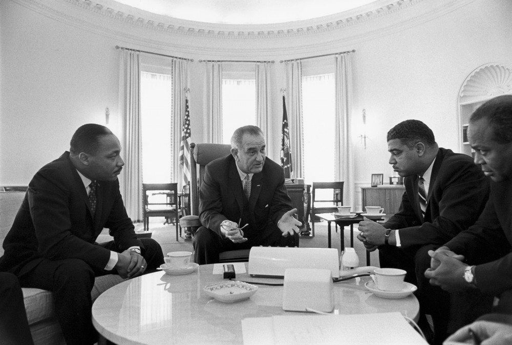 Lyndon B. Johnson sitting in the Oval Office with Martin Luther King Jr. and other black leaders.