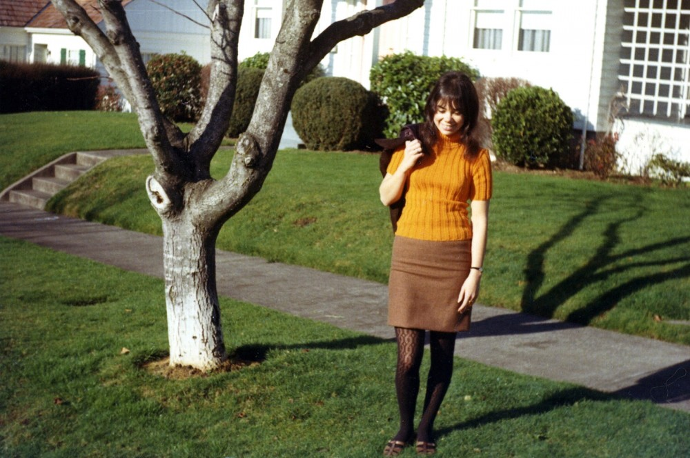 A woman wearing an orange turtleneck sweater, a brown skirt that reaches mid-thigh, and patterned tights.