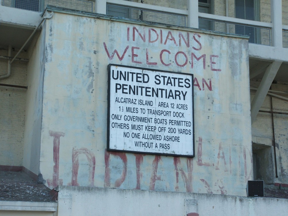 A sign on the wall of Alcatraz labeling the building as a United States Penitentiary. The sign is posted over painted words that say Indians Welcome.