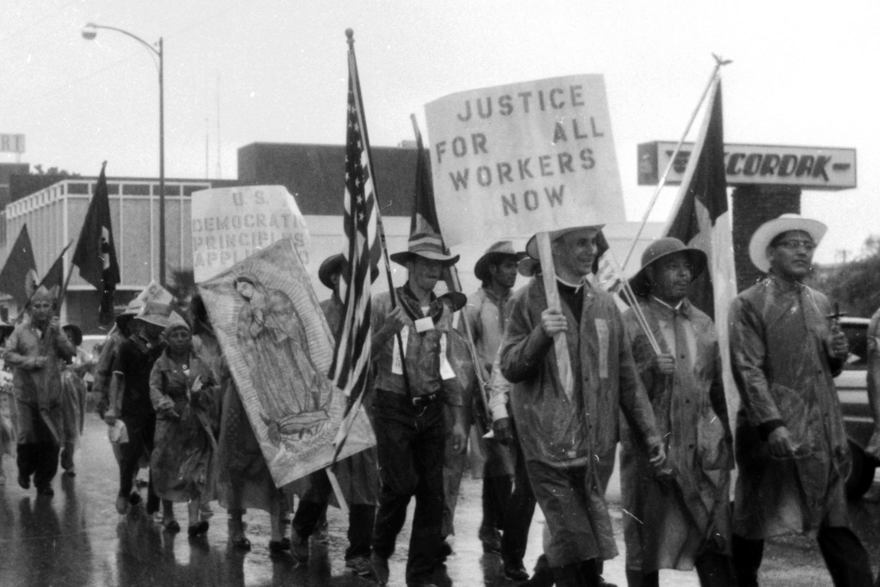People, many wearing cowboy hats, carry flags and signs. One sign says Justice for All Workers Now. Another sign shows an image of the Virgin Mary.