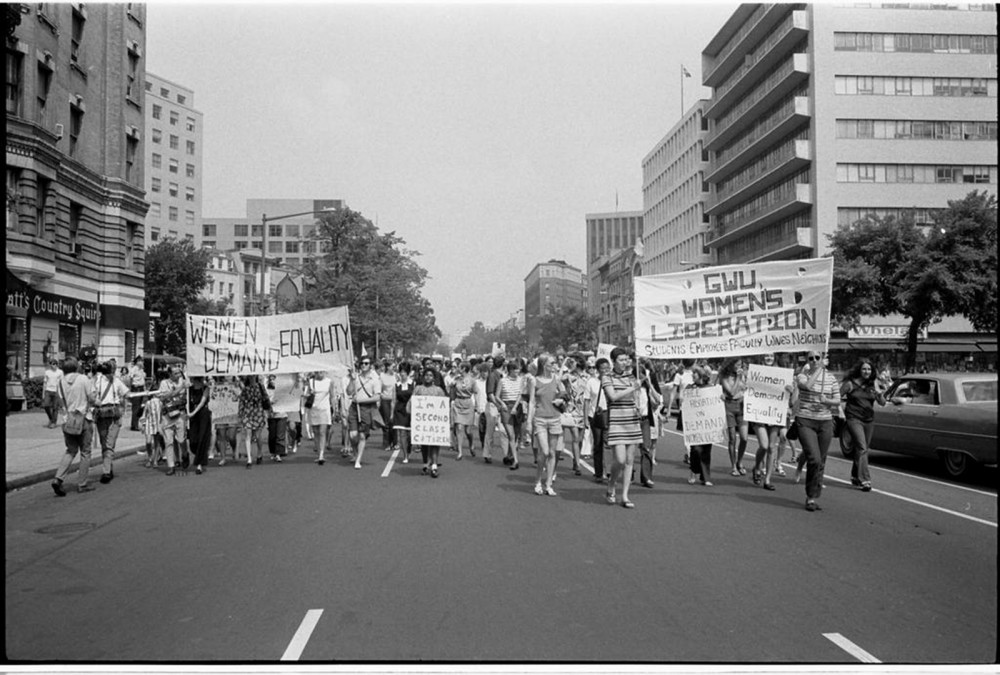 A crowd of women marching down the street of a city and bearing signs asking for womens' equality.