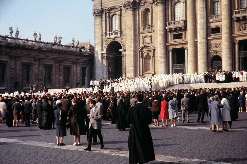 A group of robed Catholic leaders outside a Catholic church while a crowd looks on.