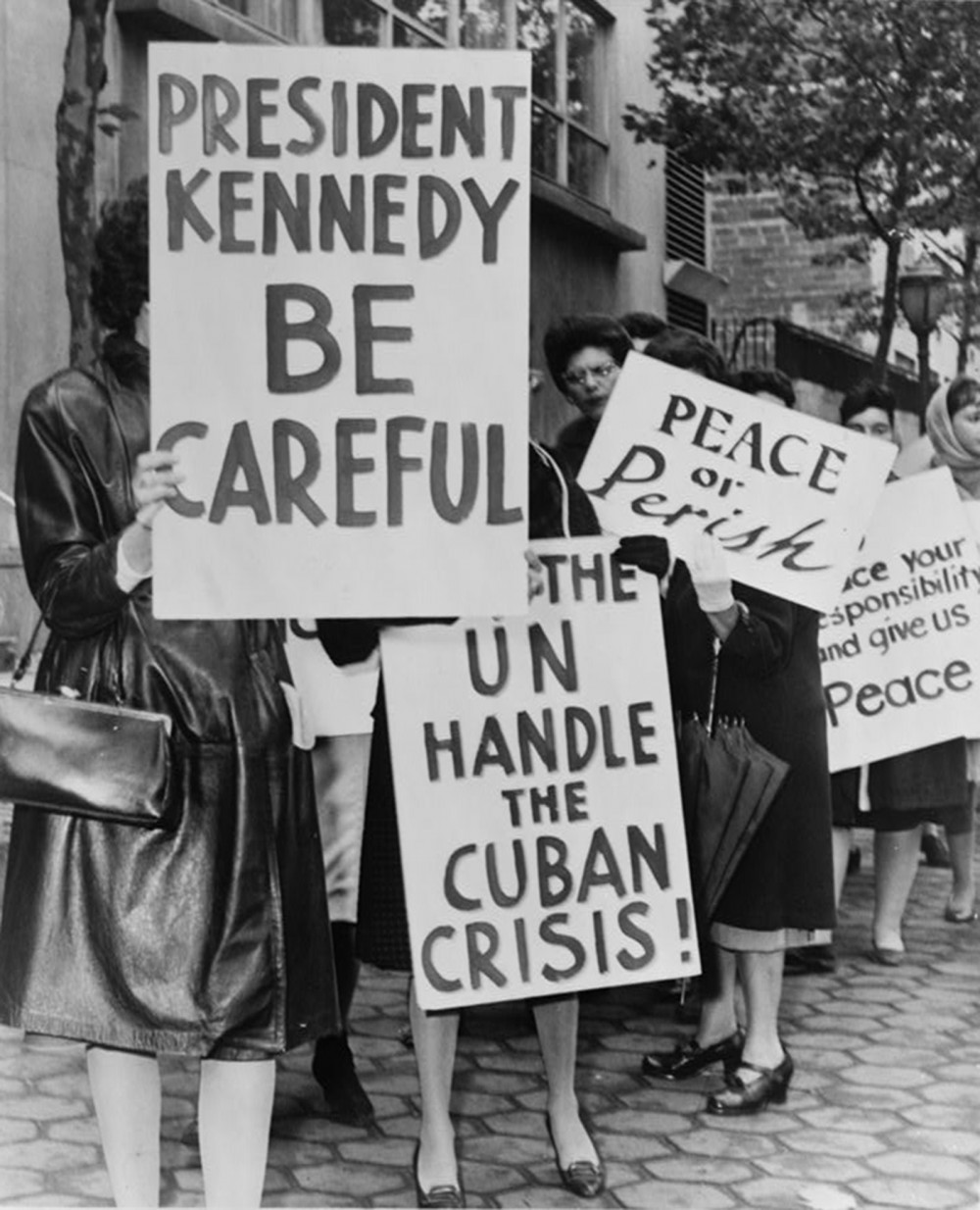 A gathering of women holding signs asking for peace and urging caution.