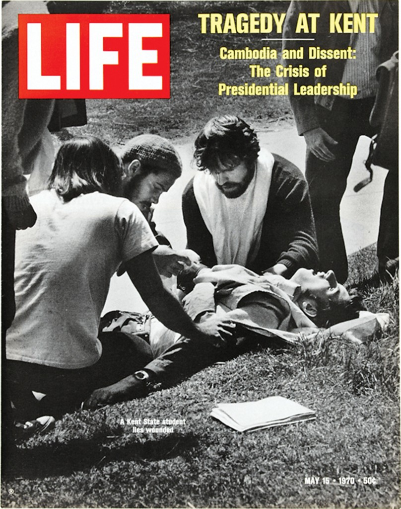 Cover of Life magazine. Three students are gathered around another student who is injured.