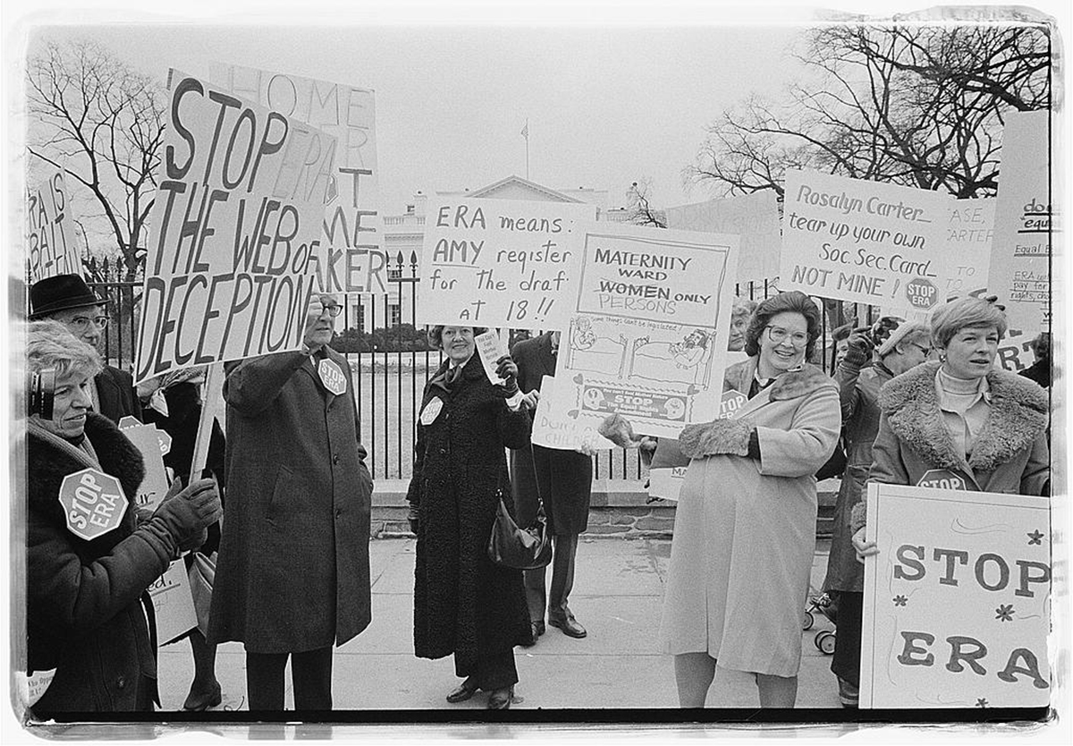 People holding signs opposing the ERA in front of the White House.