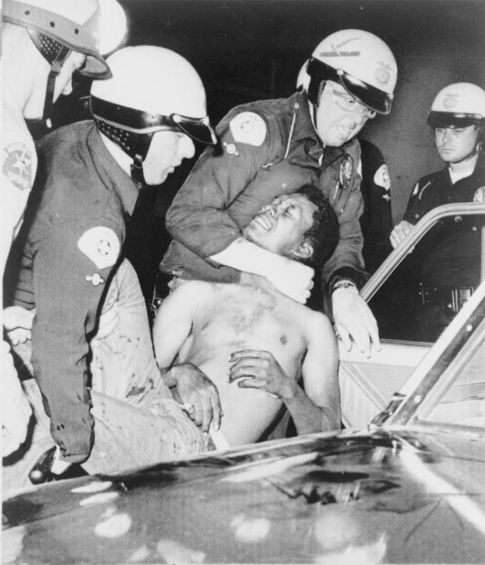 White police officers carry a black rioter into their car. One officer has his arms wrapped around the rioter's knees, and another officer has his arms wrapped around the rioter's neck.