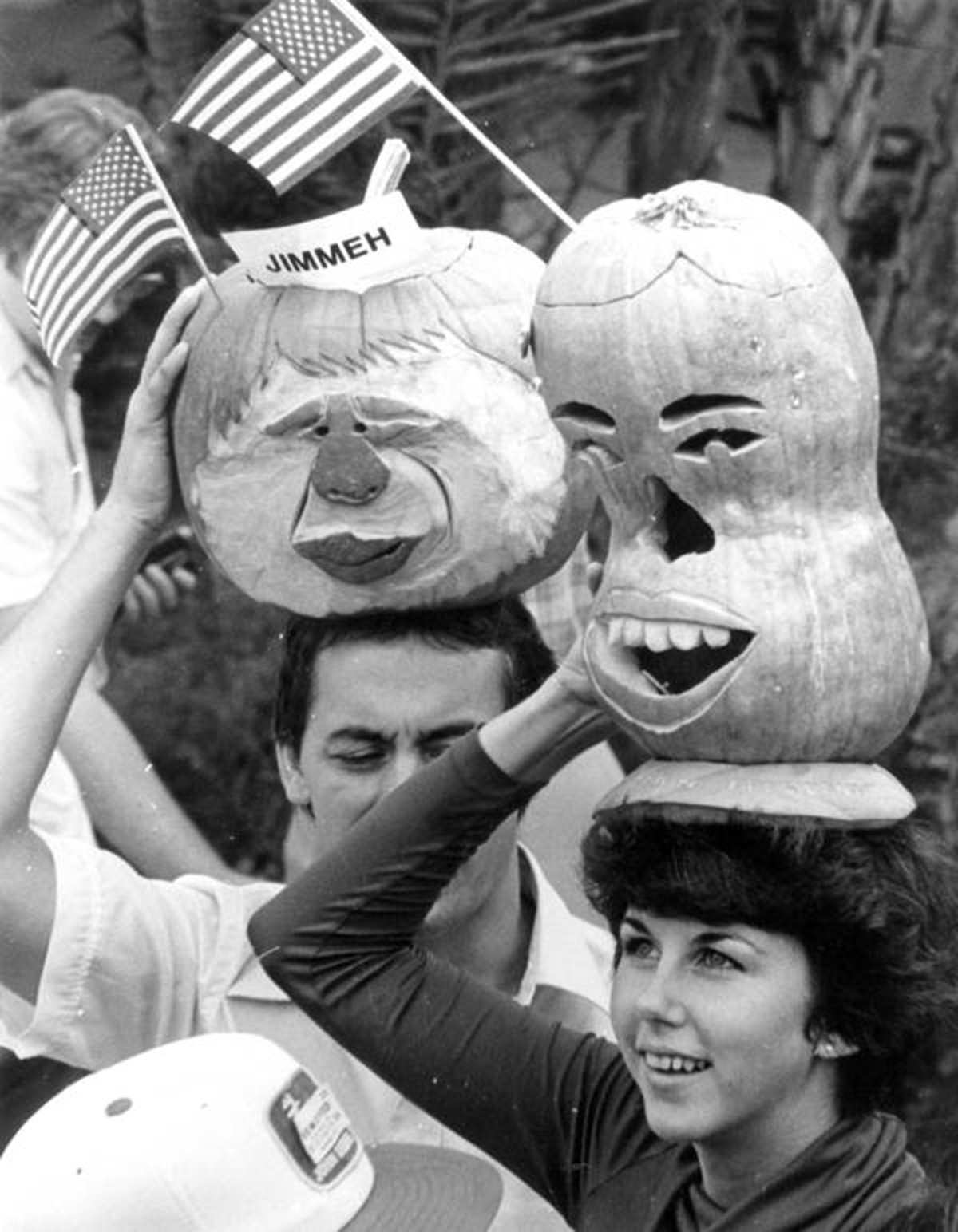 People balancing pumpkins carved into caricatures on their heads.