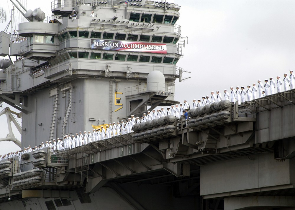 A large ship with a long line of uniformed men at attention. A banner above them reads Mission Accomplished.