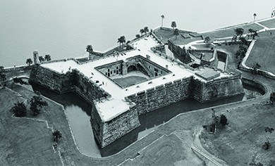 An aerial photograph shows the Spanish fort of Castillo de San Marcos, a square, high-walled structure facing the water and including a surrounding moat.