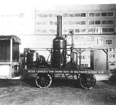 "A photograph of a replica of the Tom Thumb steam locomotive is shown. On its side are painted the words ""Peter Cooper's 'Tom Thumb' 1829–30 Baltimore and Ohio R.R."""