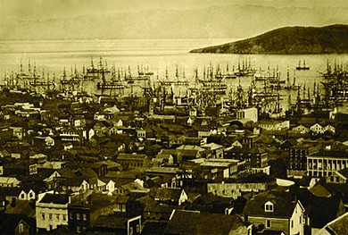 A photograph shows an aerial view of the port of San Francisco. The streets are crowded with houses, and the water teems with ships.