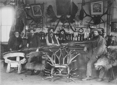 A photograph shows the interior of a saloon. Several chairs constructed of wood, hides, and antlers sit in front of a bar. Several customers sit or stand at the bar. Another man stands behind the bar, along with bottles of liquor, several framed images, and a variety of decorations and wall hangings.
