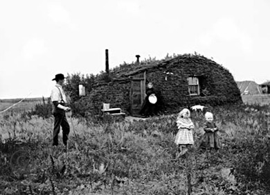 A photograph of a sod hut is shown. Before it stand a farmer, his wife, and two children.