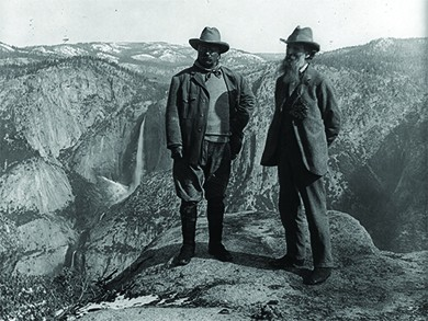 A photograph shows Theodore Roosevelt and John Muir standing atop a precipice in Yosemite National Park.