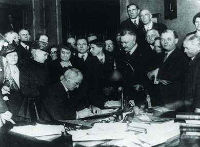A photograph depicts Governor James P. Goodrich signing a bill, surrounded by a large group of men and women.