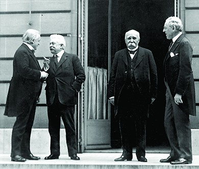 A photograph shows David Lloyd George, Vittorio Orlando, Georges Clemenceau, and Woodrow Wilson conversing outside of a building at the Paris Peace Conference.