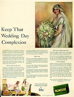 "An advertisement headlined ""Keep That Wedding Day Complexion"" features an illustration of a rosy-cheeked, elaborately dressed bride. An image of Palmolive soap is shown alongside a lengthy description of the soap's benefits. At the bottom, to illustrate that the soap contains oils used by Cleopatra, an image depicts two rosy-cheeked, white women dressed in flowing garments and seated in a room whose décor is reminiscent of ancient Egypt."