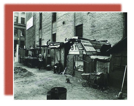 A photograph shows a row of urban shanties, with several of their inhabitants sitting outside.