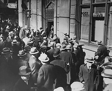 A photograph shows a large crowd of men and women waiting outside of a bank.