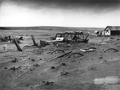 A photograph shows an abandoned farmhouse and farm equipment that were largely buried under dust.