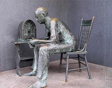 A sculpture shows a man sitting in a chair beside a radio.