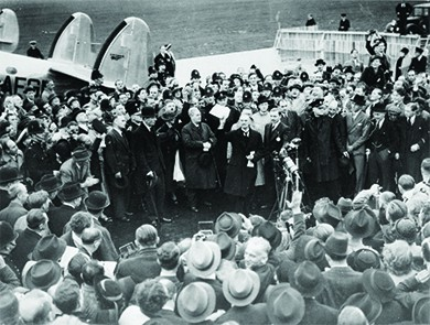 A photograph shows Neville Chamberlain immediately following his arrival in England, where he addresses an enthusiastic crowd of officials and press.