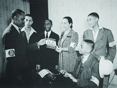 "A photograph shows five black men and a black woman participating in the Double V campaign. A young man sits at a typewriter, and the woman hands a man a pamphlet, the cover of which reads ""This is a [Double V insignia] Home."" All wear armbands."