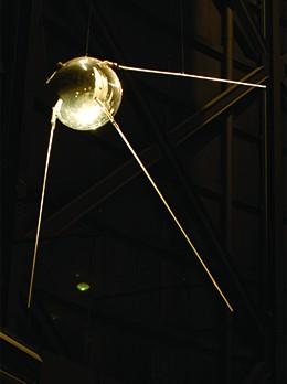 A photograph shows a replica of Sputnik.