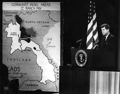 "A photograph shows President Kennedy standing at a podium delivering a speech. Beside him hangs a large map of Southeast Asia, labeled ""Communist Rebel Areas/22 March 1961."""