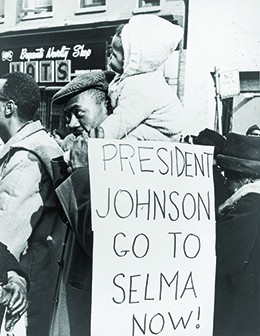 "A photograph shows a group of African Americans marching on the street in Selma, Alabama. In the foreground, a man with a small child on his shoulders carries a sign that reads ""President Johnson/Go to Selma now!"""