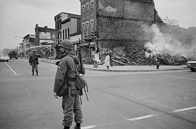 A photograph shows a street, deserted but for one pedestrian and several men in riot gear. The ruins of a building are visible on the corner.