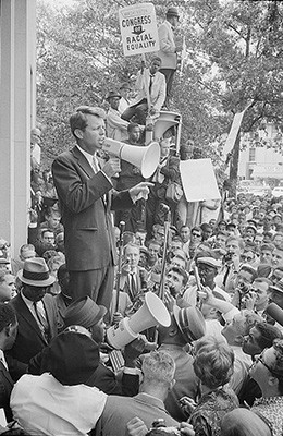 A photograph shows Robert Kennedy speaking to a large crowd through a megaphone.