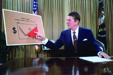"A photograph shows Reagan sitting at a desk, gesturing at a large chart labeled ""Your Taxes."""