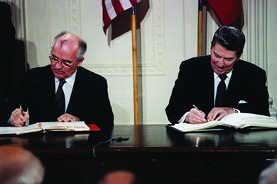 A photograph shows Mikhail Gorbachev and Ronald Reagan sitting beside one another as they sign the INF Treaty.