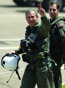 A photograph shows George W. Bush walking with naval flight officer Lt. Ryan Phillips following the president's arrival on the USS Abraham Lincoln. Bush wears a flight suit and gives a victory symbol to the cameras with his hand.