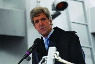 A photograph of John Kerry speaking into a microphone is shown.