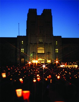 A photograph shows a massive crowd gathered in darkness in front of a large university building, holding candles.