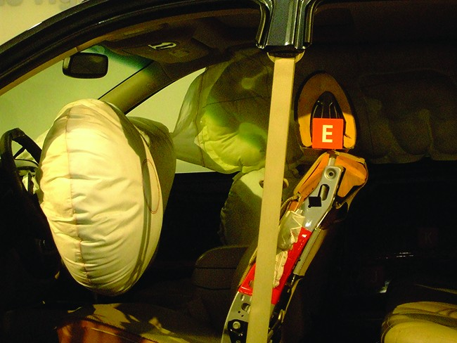 This photograph shows the inside of an automobile from the driver's side area. The image shows inflated airbags positioned just in front of the driver's and passenger's seats and along the length of the passenger side over the windows. A large, round airbag covers the steering wheel.